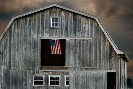 American flag flying in a hayloft window.