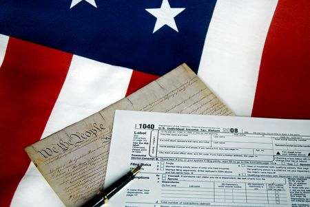 Tax form and the copy of the U.S. Constitution on a flag.