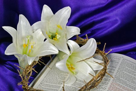 Easter lilies and crown of thorns on an open Holy Bible.