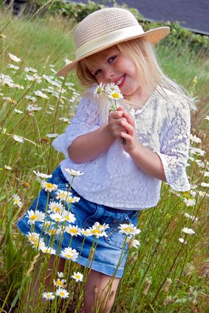 Shy little blond girl with daisy bouquet.