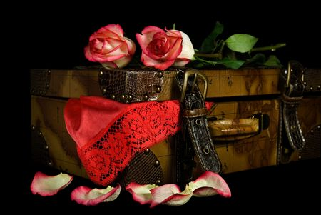 Red lace lingerie and roses with old suitcase.