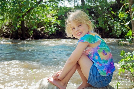 child on river rock