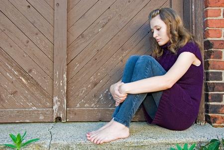 teenage girl huddled in old doorway