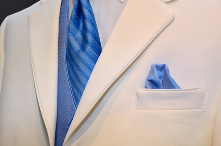 Blue tie and vest accenting a white tuxedo.