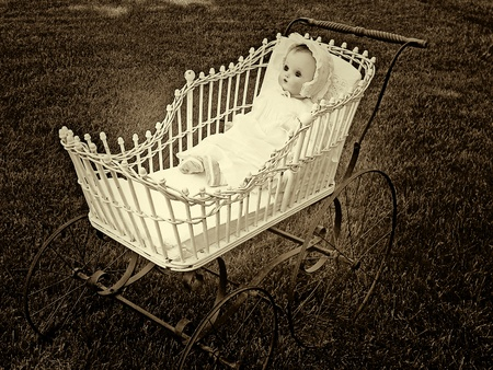 Vintage doll in old-fashioned baby buggy in sepia
