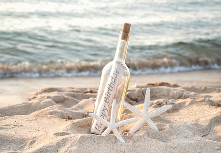 Foto per pair of white starfish with happy birthday message in a bottle on beach sand - Immagine Royalty Free