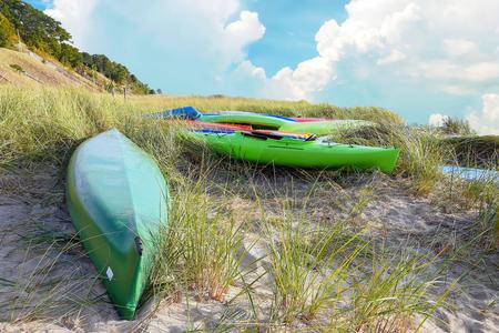 Foto de colorful kayaks in dune grass on Lake Michigan beach - Imagen libre de derechos