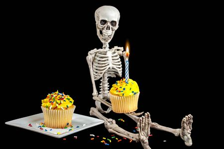 Photo pour skeleton holding a birthday cupcake with yellow frosting and sprinkles isolated on black - image libre de droit