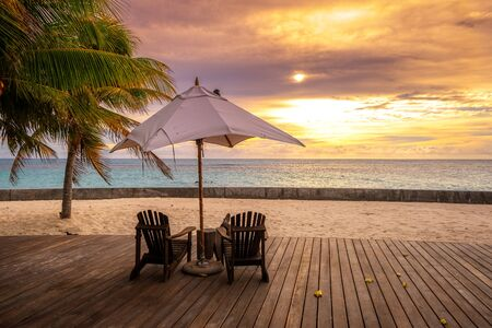 Photo pour Umbrella and deck chairs on the beautiful tropical beach and sea at sunset time for travel and vacation - image libre de droit