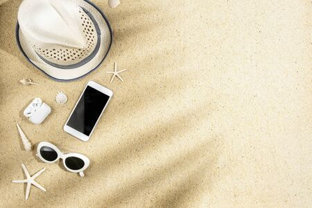 Photo pour White hat, sunglasses, phone, headphone, sea shells and starfish with palm branch shadow on sand background, copy space, flat lay - image libre de droit