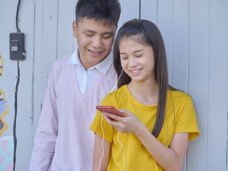 Photo for Young teens men and women use their smartphones outdoor at the park. - Royalty Free Image