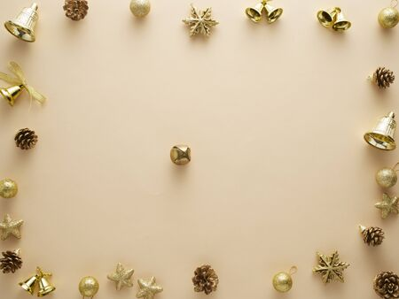 Christmas decorations in gold colors on beige background. Holiday and celebration concept for postcard design. Top view, space for text.