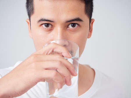 Photo pour Close-up of young man in white t-shirt drinking water from a glass - image libre de droit