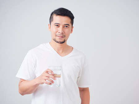 Photo pour Handsome young man in a white T-shirt holding a glass of drinking water while standing in studio setting - image libre de droit