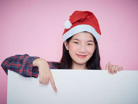 Photo pour Cute teenage gir in santa hat pointing finger on blank poster while standing on pink background. - image libre de droit