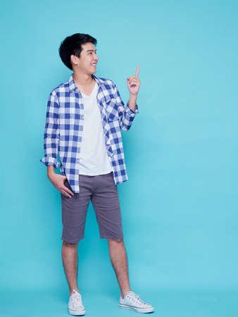 Photo pour Handsome young men pointing on blue background. Space for text - image libre de droit