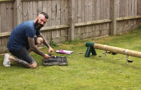 A man building a childrens wooden swing in a garden