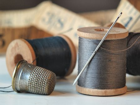 Close up of thread spools, needle, and thimble with a tape measure in the background.