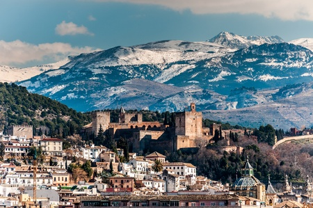 Winter view of famous Alhambra in front of Sierra Nevada mountains topped with show