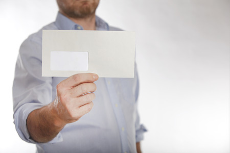 Man in a blue shirt holds a letter into the camera