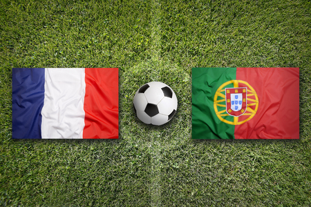 France vs. Portugal flags on a green soccer field