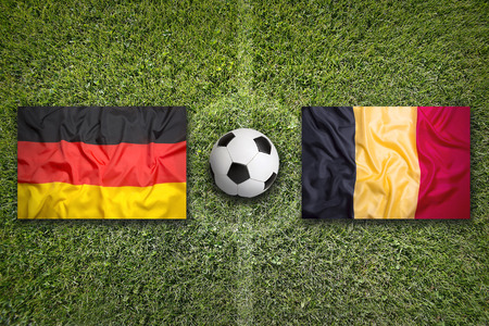 Germany vs. Belgium flags on a green soccer field