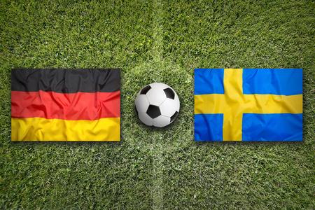 Germany vs. Sweden flags on a green soccer field