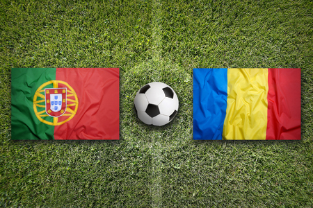 Portugal vs. Romania flags on a green soccer field