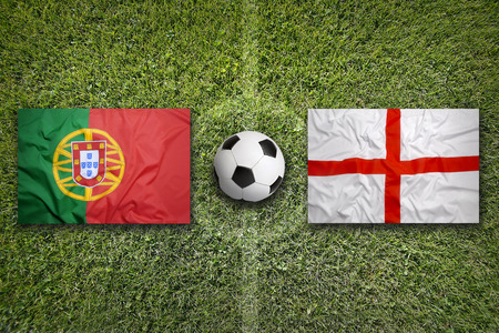 Portugal vs. England flags on a green soccer field