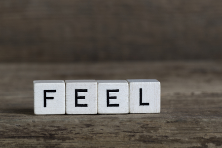 Feel, written in cubes on a wooden background