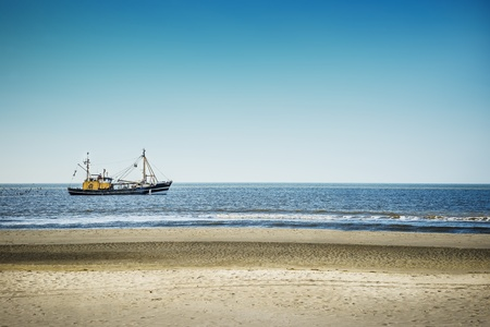 Trawlers in the North Sea on the beach of St  Peter-Ording on a sunny day