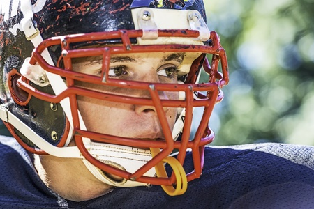 Portrait of a American Football Player with a heavily worn helmet