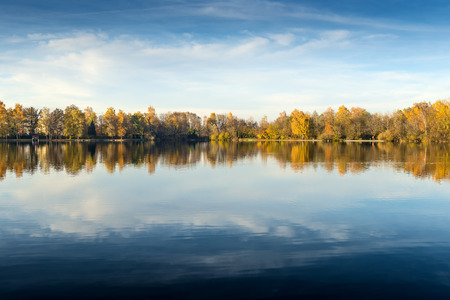 Picture of a lake and trees with colorful leaves on an evening in autumn in Bavaria