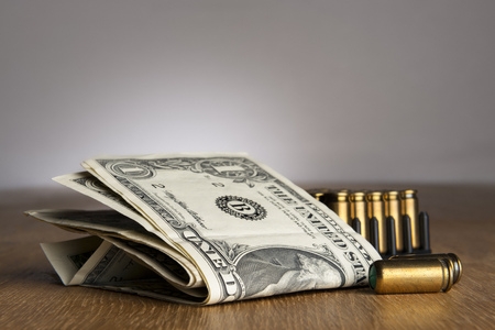 Image of dollar bills with pistols cartridges on a table