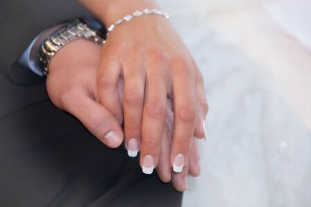 Photo pour Bride and groom hold their hands romantically - image libre de droit