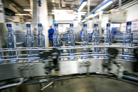 Photo pour Many bottles on conveyor belt in factory, production of russian traditional alcohol drink vodka - image libre de droit