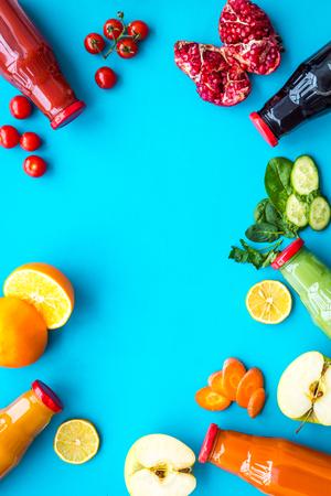 Photo pour Bottles with fresh carrot, tomato, apple, cucumber, lemon, pomegranate juices on blue top view copyspace - image libre de droit