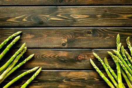 Photo pour Asparagus steams frame on dark wooden background top-down. - image libre de droit