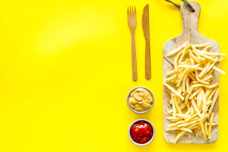 French fries served on cutting board on yellow table top-down.の素材 [FY310140553839]