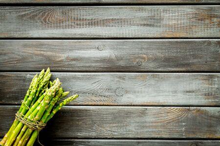 Photo pour Bunch of asparagus steams on dark wooden - image libre de droit