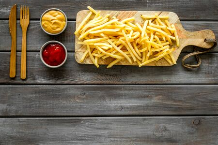 French fries served on cutting board on wooden table top-down.の素材 [FY310142568848]