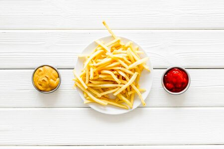 Fast food symbol. French fries on plate on white wooden table top-down copy spaceの素材 [FY310142610791]