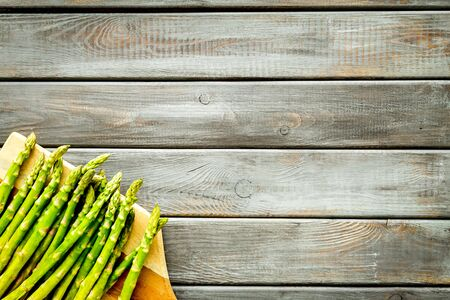 Photo pour Cooking asparagus. Fresh steams on cutting board on dark wooden background top-down copy space - image libre de droit