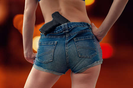 Photo for Young girl in denim shorts is holding a black pistol tucked into his belt behind her. - Royalty Free Image