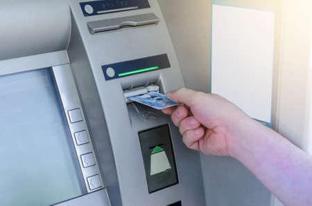 Photo pour Man hand puts card, press button gray ATM - image libre de droit