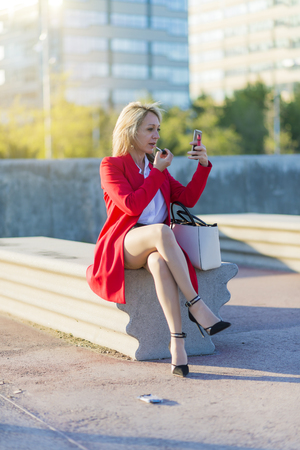 Photo pour Trendy blonde woman using her lipstick sitting on a bench and using the smartphone as a mirror - image libre de droit