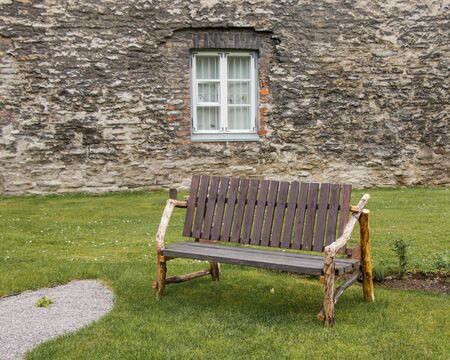 Unusual rural wood bench made of boards and branches against the background of the stone wall of the old city in Tallinn, Estonia.