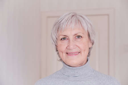 Photo pour A close-up portrait of a smiling and looking at the camera elderly Caucasian woman with short gray hair on a light background. - image libre de droit