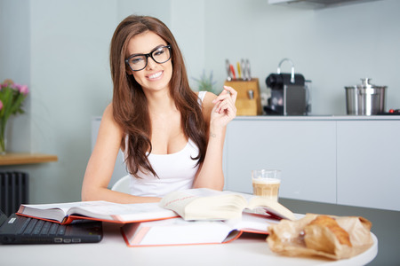 a happy young woman studying in kitchen