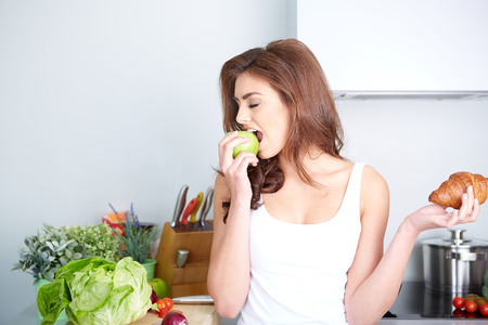 Diet. Dieting concept. Healthy Food. Beautiful Young Woman choosing between Fruits and Sweets